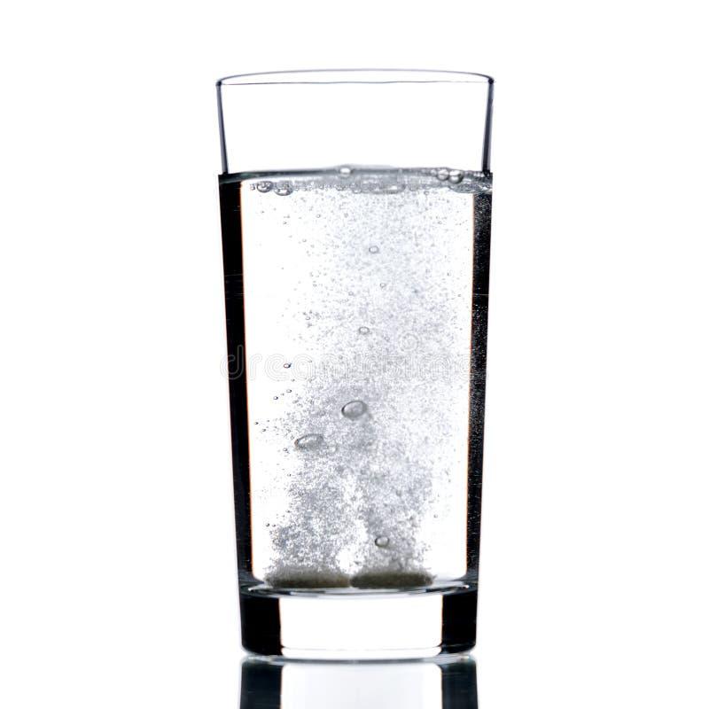 Zwei sprudelnde Pillen im Glas des Wassers Getrennt auf einem weißen Hintergrund stockbild