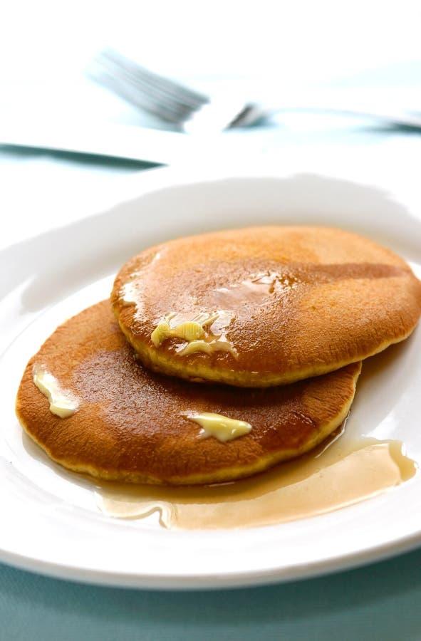 Zwei Stücke des frisch gekochten Pfannkuchens nieselten mit Ahornholzsirup lizenzfreie stockfotos