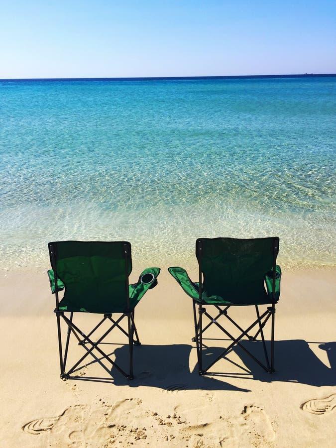 Zwei Stühle auf dem Strand stockfotos