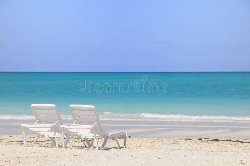Zwei Stühle auf tropischem Strand stockfotos