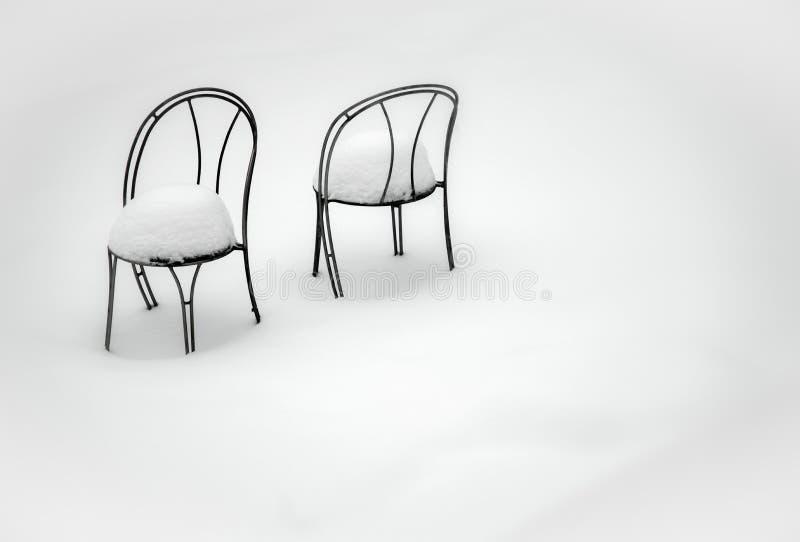 Zwei Stühle bedeckt in den Schneehügeln, sitzend in frisch gefallenem Schnee lizenzfreies stockfoto