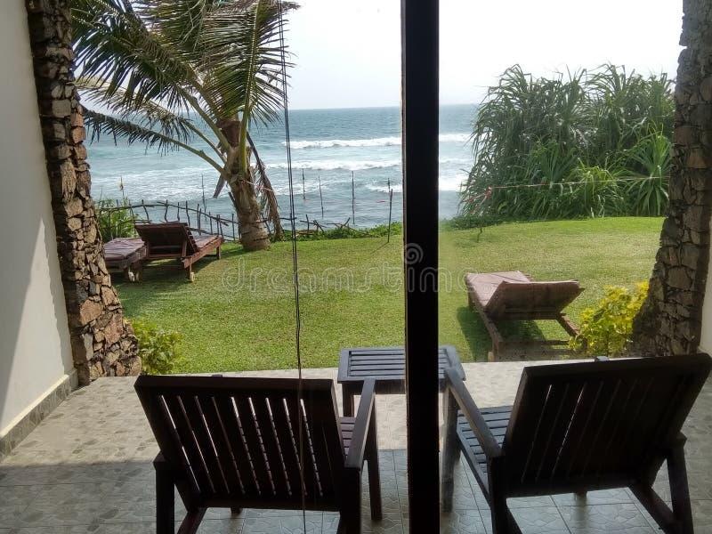 Zwei Stühle nahe einem großen Fenster, welches die Palmen, die sunbeds und den Indischen Ozean übersieht lizenzfreie stockfotos
