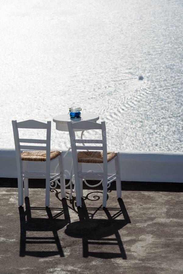 Zwei Stühle, Tabelle und erstaunliche Ansicht über Ägäisches Meer, Santorini, Griechenland stockfotografie