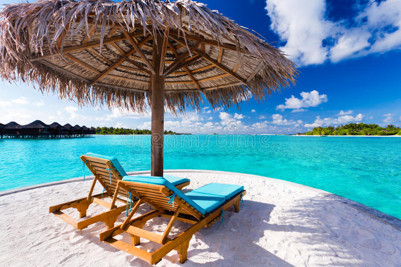 Zwei Stühle und Regenschirm auf tropischem Strand lizenzfreie stockfotos
