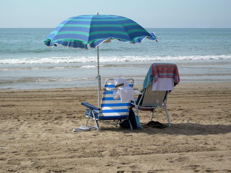 Zwei Stühle Unter Einem Regenschirm Lizenzfreies Stockfoto