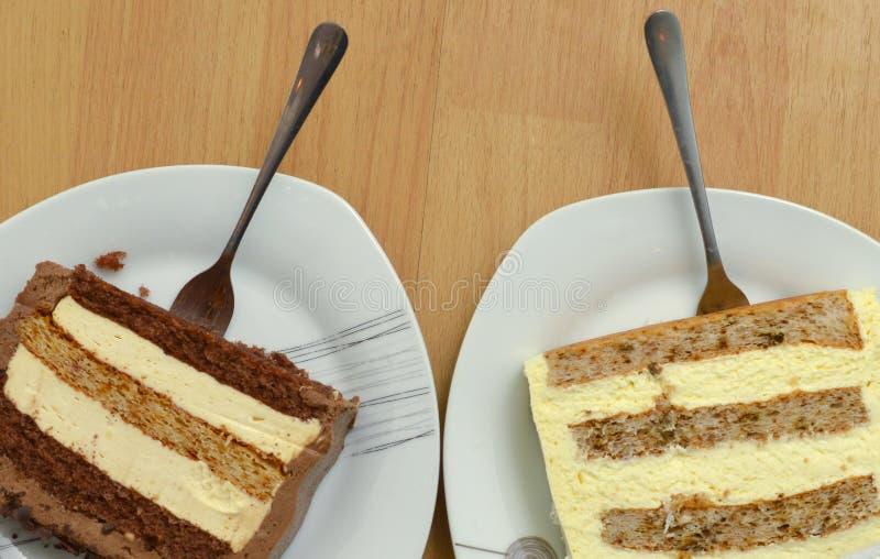 Zwei St?cke eines Kuchens und des Baklava in drei Platten auf h?lzernem Hintergrund, s??es Nahrungsmittelkonzept stockbilder
