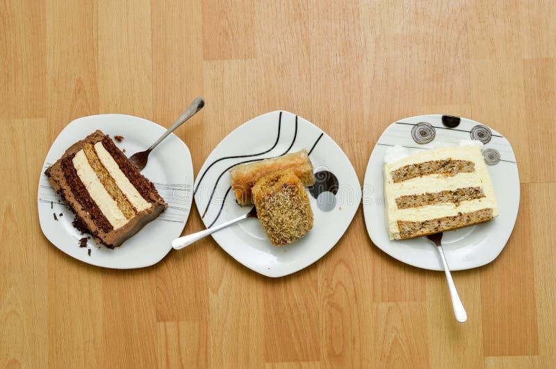 Zwei St?cke eines Kuchens und des Baklava in drei Platten auf h?lzernem Hintergrund, s??es Nahrungsmittelkonzept lizenzfreies stockfoto