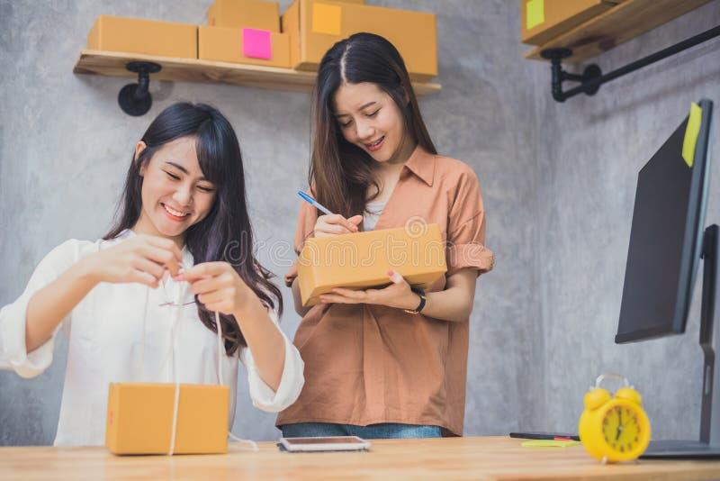 Zwei Startkleinbetriebunternehmer SME-Lagerhaus der jungen asiatischen Leute mit Paketbriefkasten Kleinunternehmer h stockfotografie