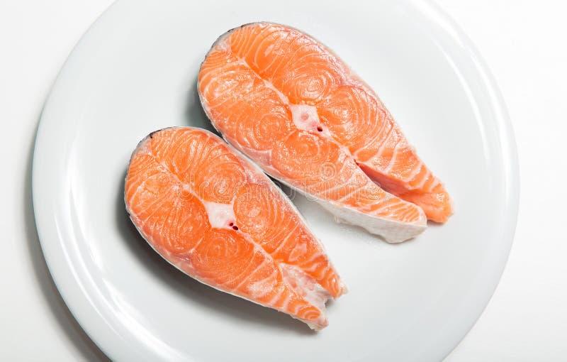 Zwei Steaks von frischen Lachsen auf einer weißen Platte stockfotografie