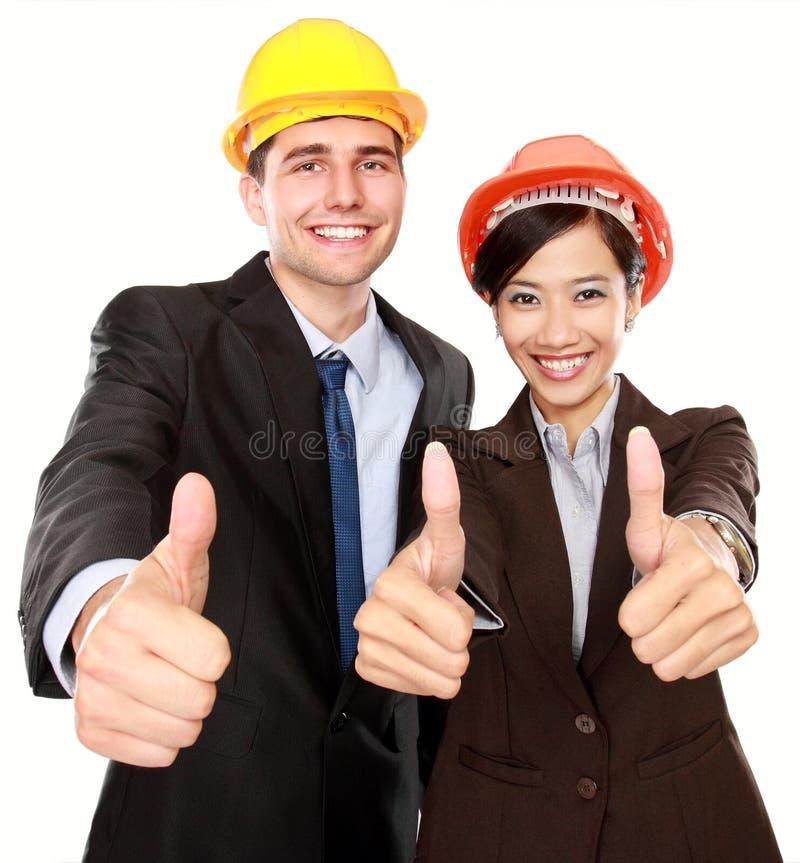 Zwei stehende Arbeitskräfte, die sich Daumen zeigen stockfotos