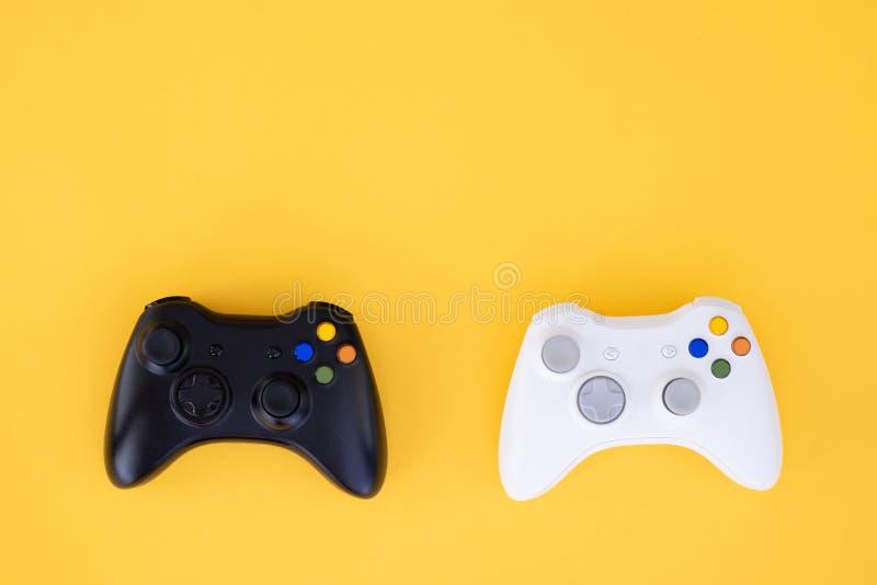 Zwei Steuerknüppel, Schwarzweiss auf einem gelben Hintergrund Das weiße und schwarze gamepad werden auf einem gelben Hintergrund  stockfotos
