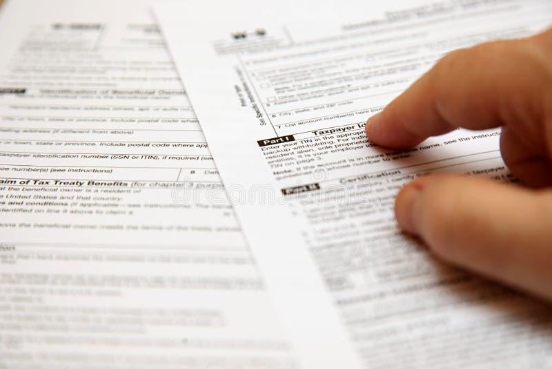 Zwei Steuerzahlerformen mit einer Hand lizenzfreie stockfotografie