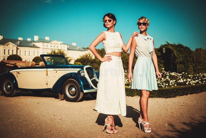 Zwei stilvolle Damen nähern sich klassischem Kabriolett lizenzfreie stockbilder