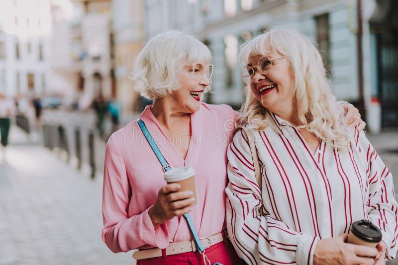 Zwei stilvolle Frauen lächeln miteinander lizenzfreie stockfotografie