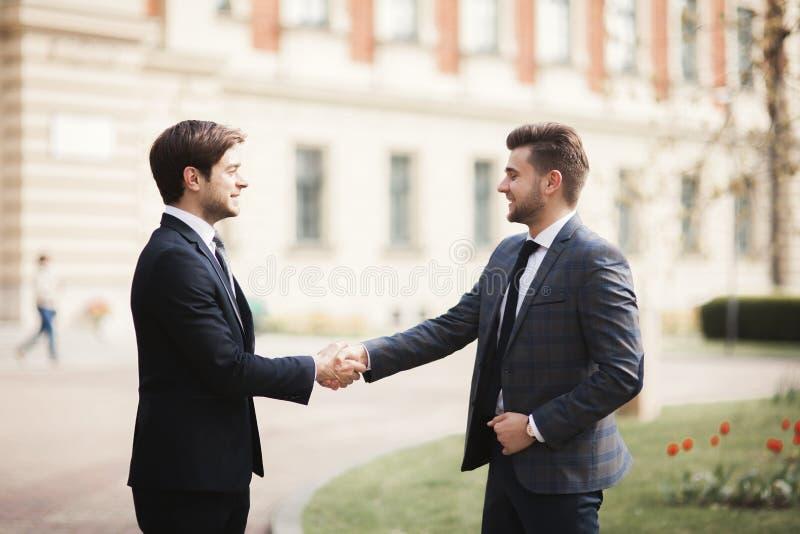 Zwei stilvolle Geschäftsmänner, die Hände in den Klagen rütteln lizenzfreie stockfotografie