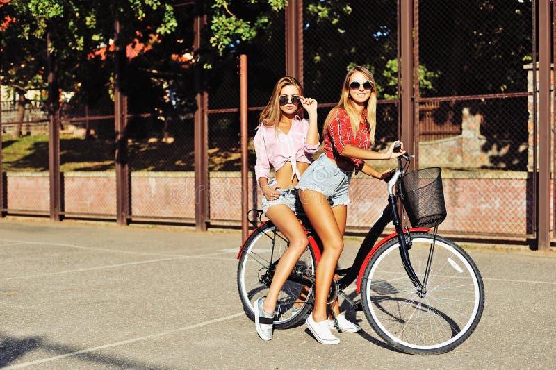 Zwei stilvolle junge und sexy Mädchen auf Fahrräder im Sommer lizenzfreies stockbild