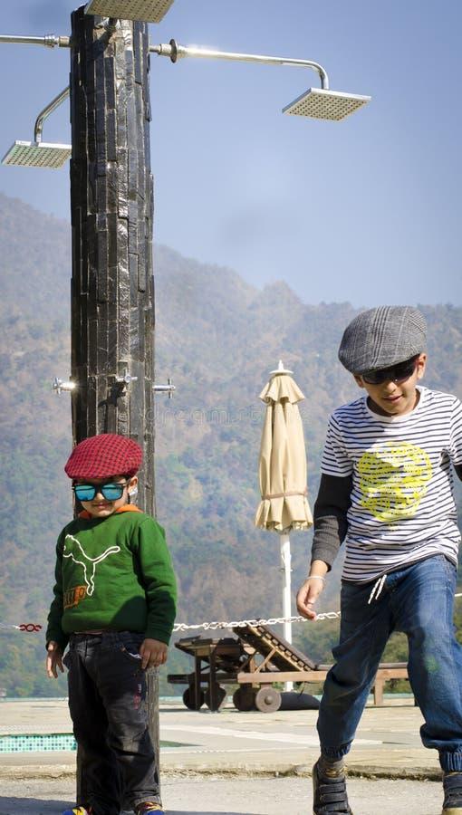 Zwei stilvolle Kinder, welche zusammen die Kappen haben Spaß tragen stockfoto