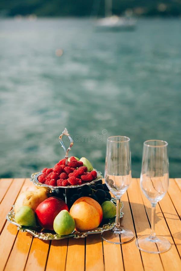 Zwei-storeyed Platte mit Früchten: Himbeeren, Pfirsich, Äpfel, Feigen stockfotos