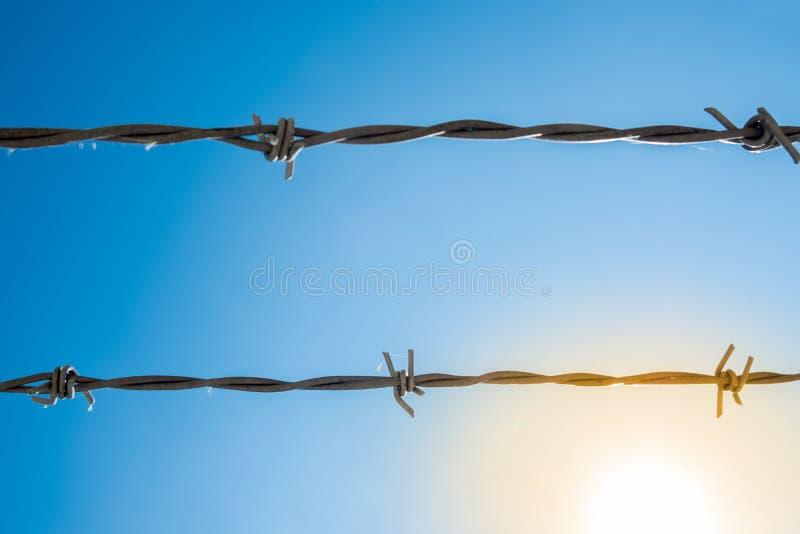 Zwei Stränge Stacheldraht mit blauem Himmel im Hintergrund und im s lizenzfreie stockfotos