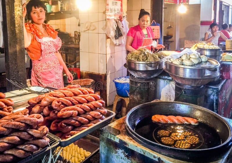 Zwei Straßenverkäufer verkaufen chinesisches traditionelles Lebensmittel in einem freien Markt in China lizenzfreies stockbild