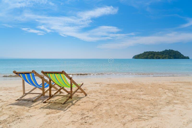 Zwei Strandstühle auf dem weißen Sand mit Meer des blauen Himmels und des Sommers stockbild