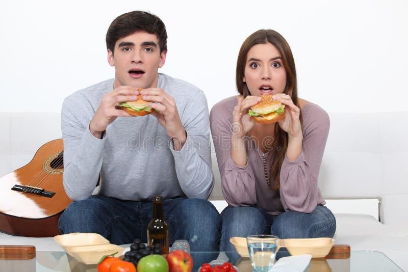 Zwei Studenten, die Burger essen lizenzfreie stockbilder