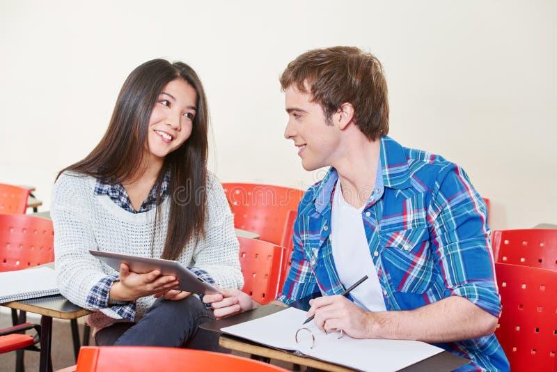 Zwei Studenten, die in einem Klassenzimmer flirten lizenzfreie stockfotos