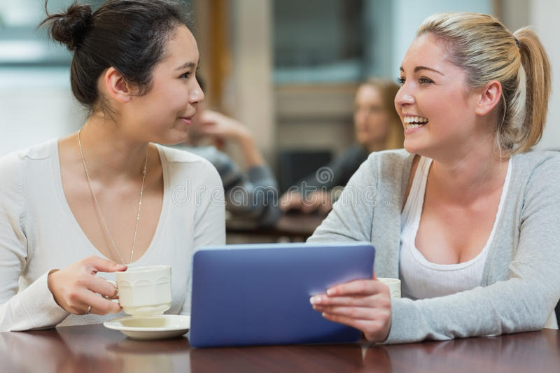 Zwei Studenten, die in einer Kaffeestube plaudern stockfotos