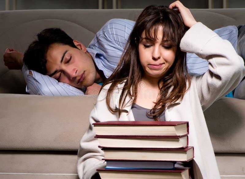 Zwei Studenten, die f?r Pr?fungen sp?t sich vorbereiten studieren stockbilder