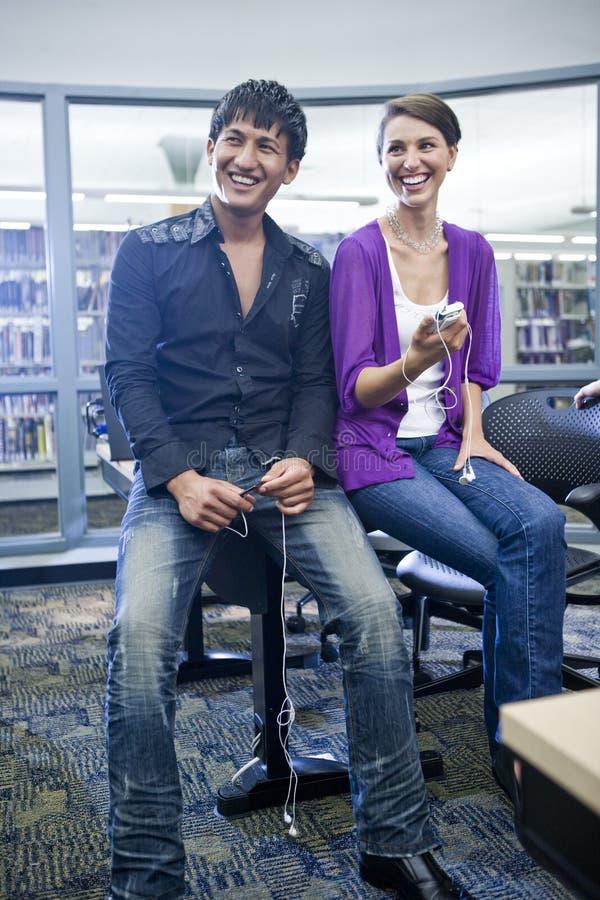 Zwei Studenten mit Musikspielern in der Bibliothek stockfotografie