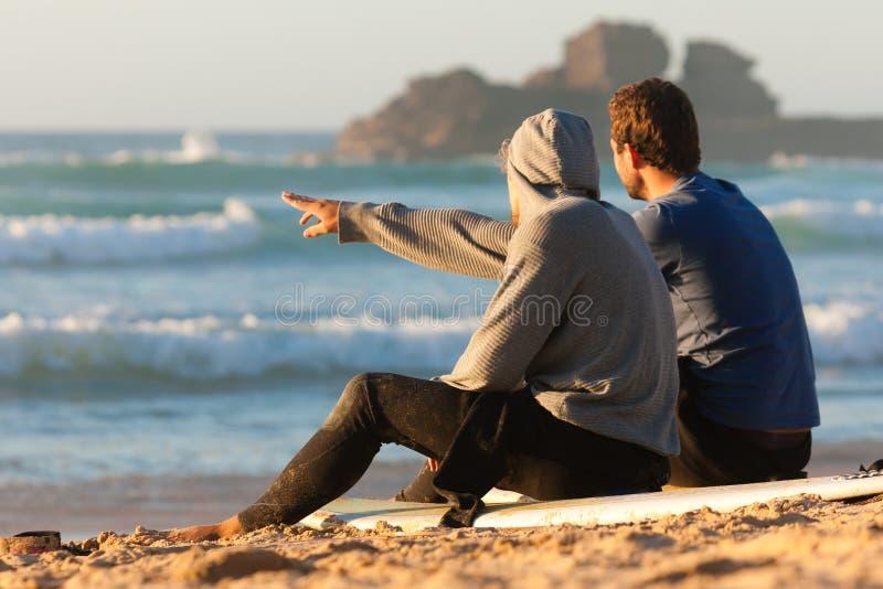 Zwei Surfer, die auf dem Strand sprechen lizenzfreie stockfotos