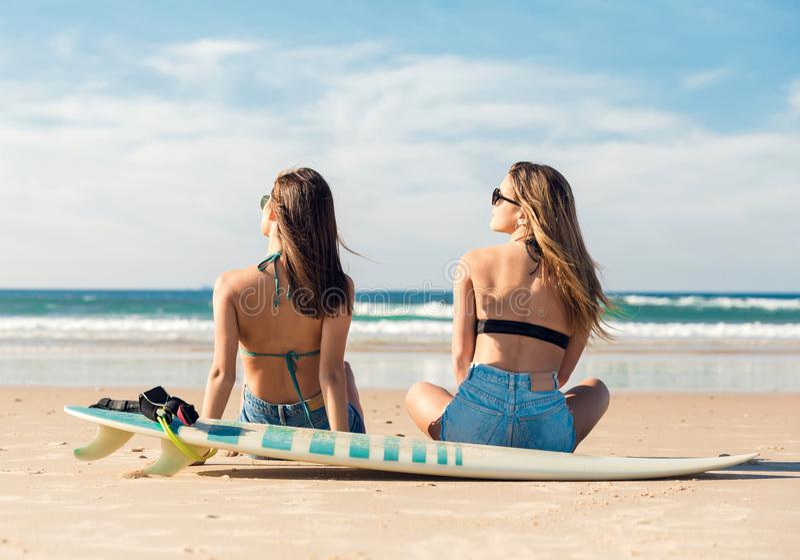 Zwei Surfermädchen am Strand stockbild