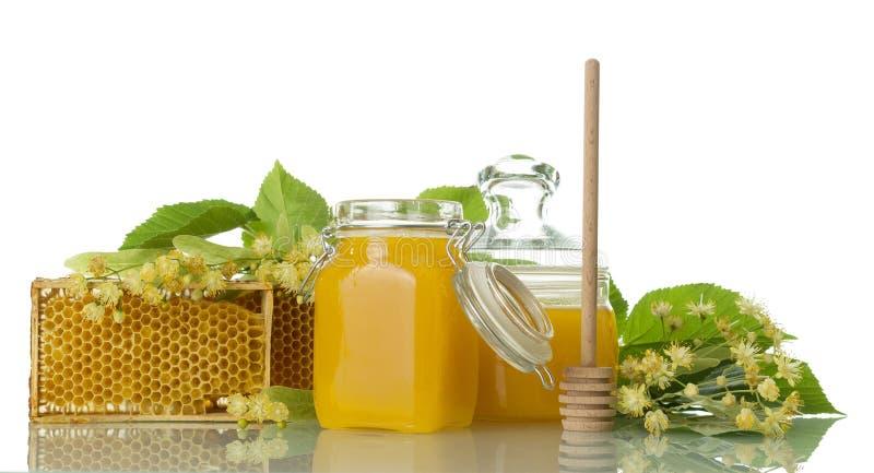 Zwei Töpfe mit dem Honig, hölzernem Löffel und der Bienenwabe lokalisiert auf Weiß stockbild