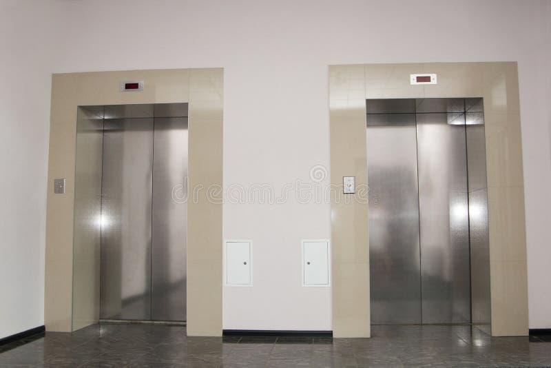 Zwei Türen von Aufzügen im modernen Geschäftsgebäude stockfotografie