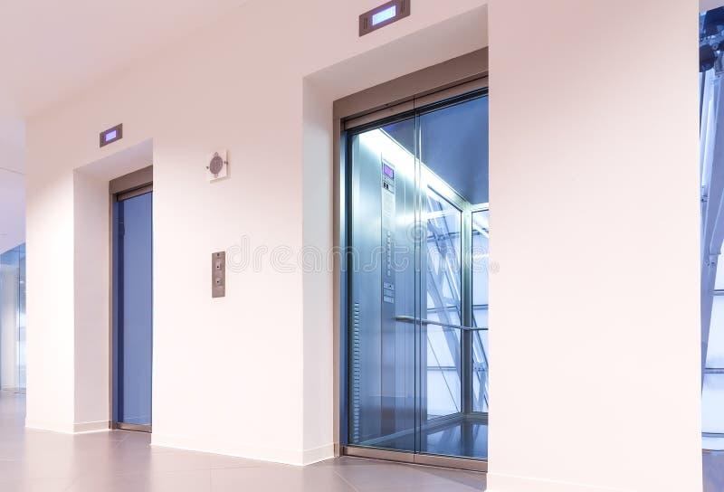 Zwei Türen von Aufzügen mit transparenten Wänden im modernen Geschäftsgebäude stockfotos