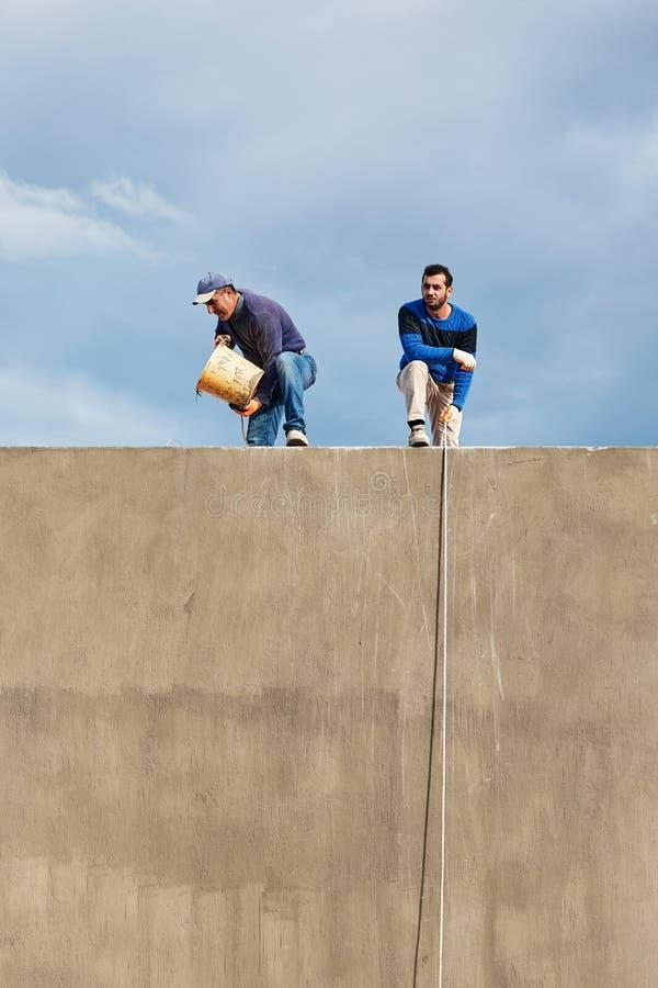 Zwei türkische Bauarbeiter, die an der Spitze eines Gebäudes arbeiten und die Eimer mit Seilen gegen einen bewölkten Himmel hochz stockfotografie