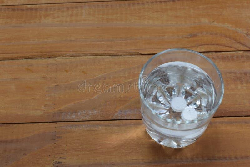 Zwei Tabletten in einem Glas Wasser lösen sich auf stockfotografie