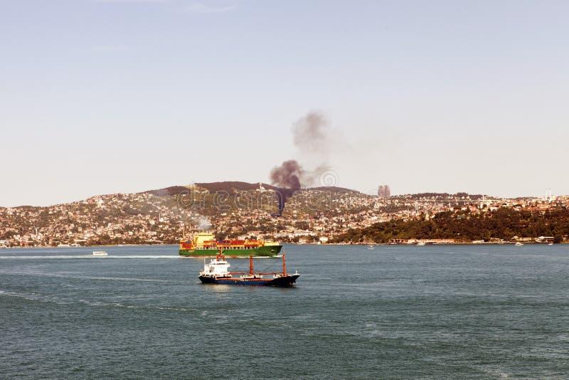 Zwei Tanker, die durch das bosphorus und ein Feuer in den Hügeln überschreiten lizenzfreies stockbild