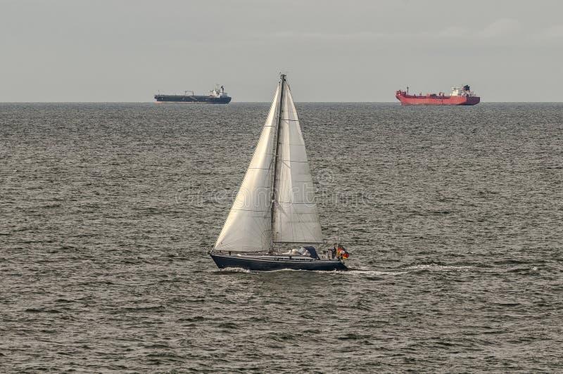 Zwei Tanker und ein Segelboot in Meer lizenzfreie stockfotos