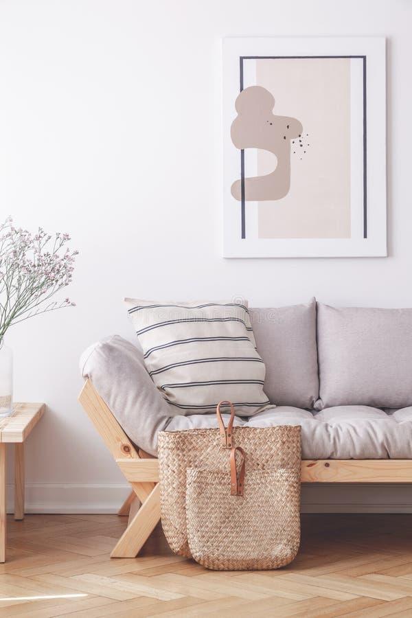 Zwei Taschen auf dem Boden der stilvollen Wohnung mit grauer Couch und gestaltetem Druck auf der Wand lizenzfreie stockfotos
