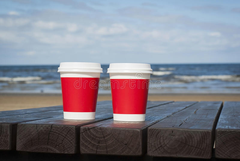 Zwei Tasse Kaffees auf der Seeküste setzen für ein Paar in der Liebe auf den Strand lizenzfreie stockfotos