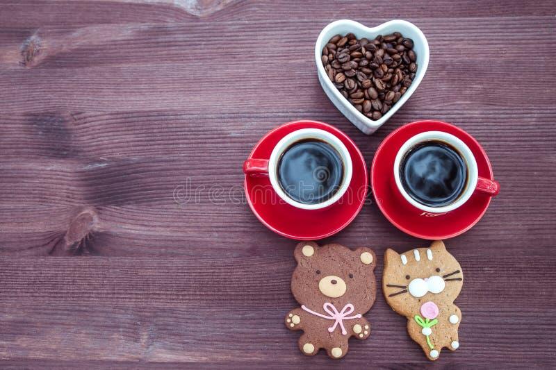 Zwei Tasse Kaffees, ein Herz mit Kaffeebohnen und Kekse in Form von Tieren stockfotografie
