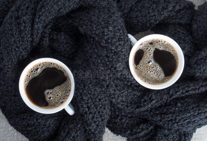 Zwei Tasse Kaffees eingewickelt im schwarzen woolen Schal lizenzfreie stockbilder