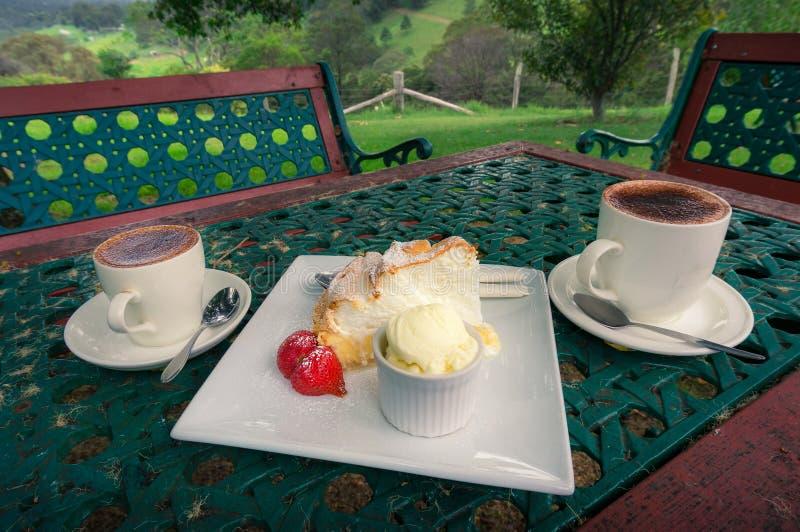 Zwei Tasse Kaffees mit Zitronenmeringekuchen, -erdbeere und -schaufel der Eiscreme stockfotos