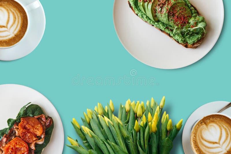 Zwei Tasse Kaffees, Sandwiche und ein Blumenstrauß von Blumen auf einer hellen Oberfläche Festliches Konzept stockfoto