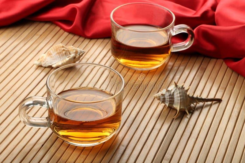 Zwei Tassen Tee auf Holztisch-Matte mit Seeoberteilen lizenzfreies stockfoto