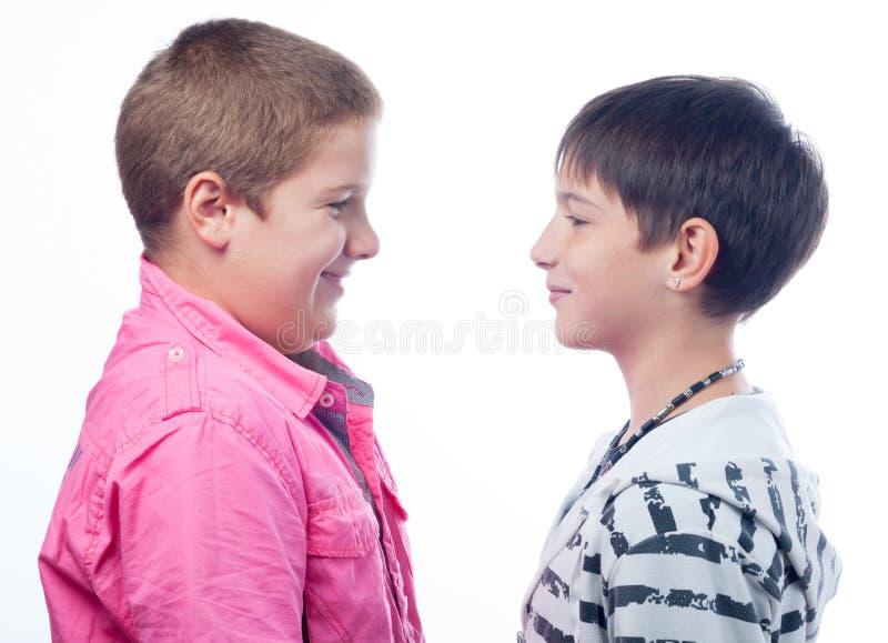 Zwei Teenager, die an einander lächeln, lokalisierten auf Weiß lizenzfreie stockfotografie