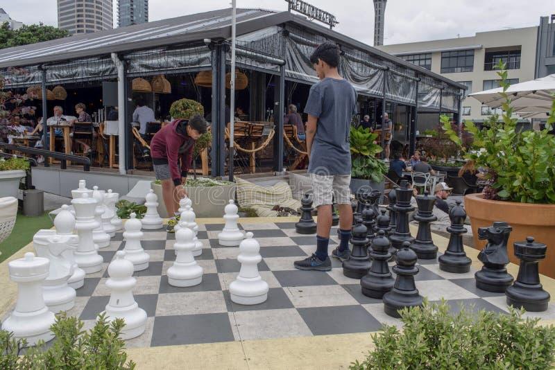 Zwei Teenager, die Schach im Freien spielen stockbild