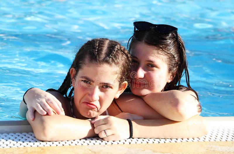 Zwei Teenagermädchen haben Spaß im Pool stockfotos