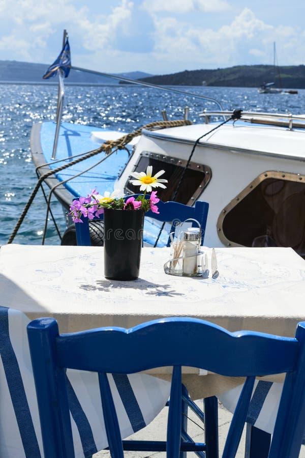 Zwei Tische und Stühle in einem gemütlichen Restaurant am Ufer des alten Hafens der griechischen Stadt Fira stockfotografie